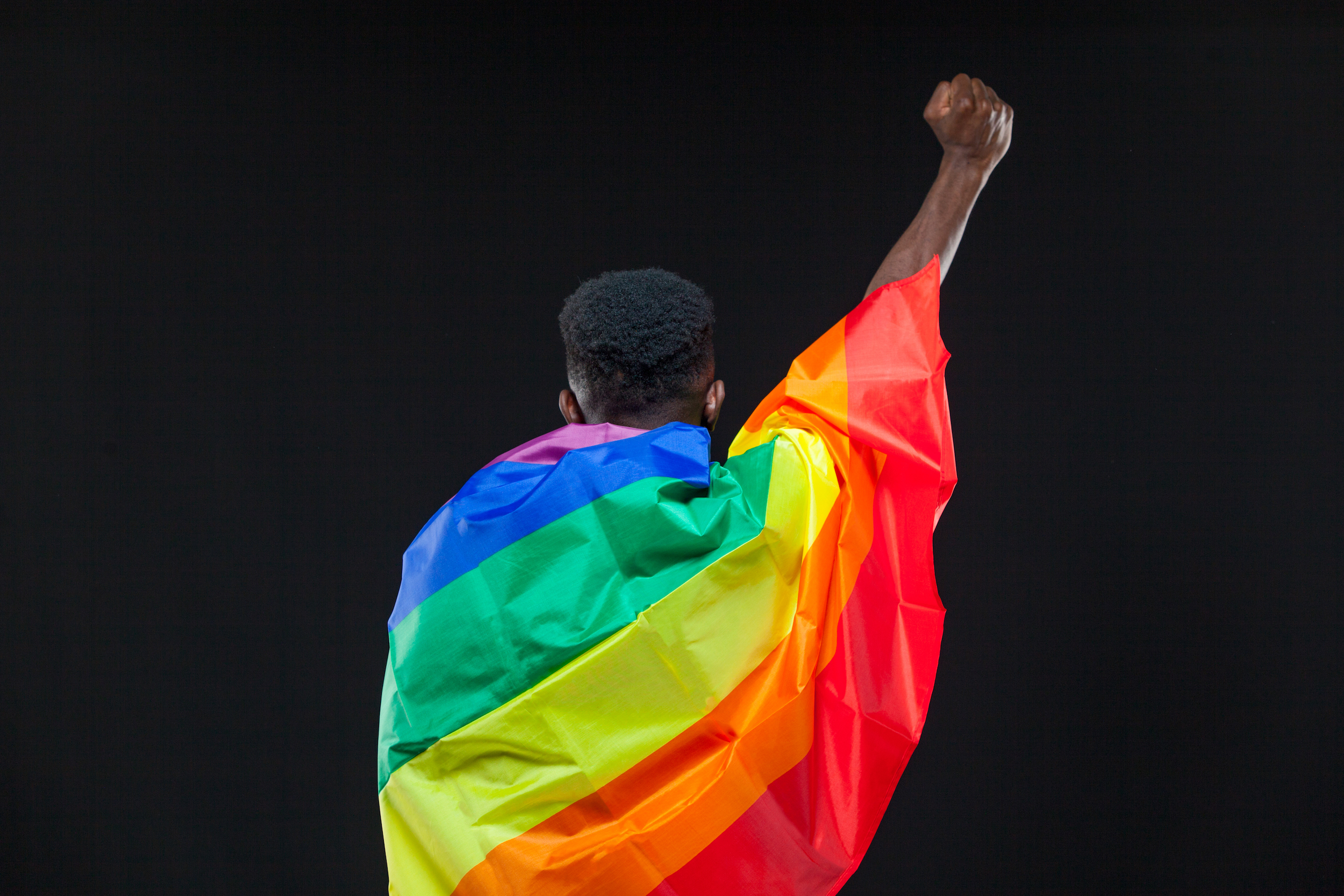 Back view of young african american man wrapped in a rainbow flag standing with raised fist isolated on black background.